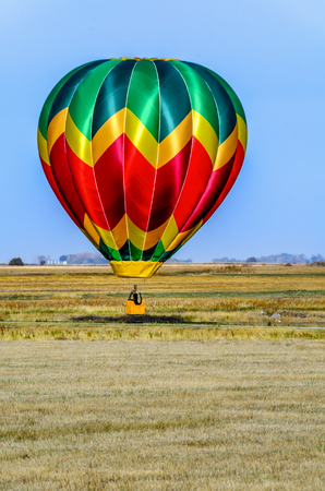 a multi-colored balloon with a basket, a flame of fire and a silhouette of a pilot flies into the blue sky over the yellow field on a summer day, a forest and metal barns for grain in the background Stock Photo