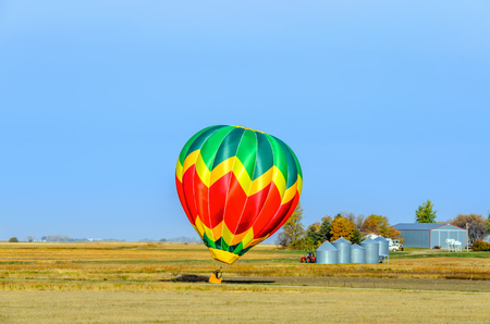 a multi-colored balloon with a basket, a flame of fire and a silhouette of a pilot flies into the blue sky over an yellow field on a summer day, a tractor, a forest, a farm and metal grain barns in the background Stock Photo
