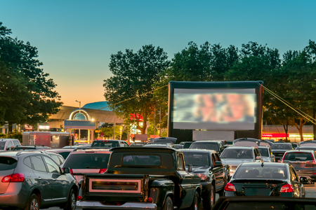 Watching movies outdoors from the car in the city parking lot on a warm summer night