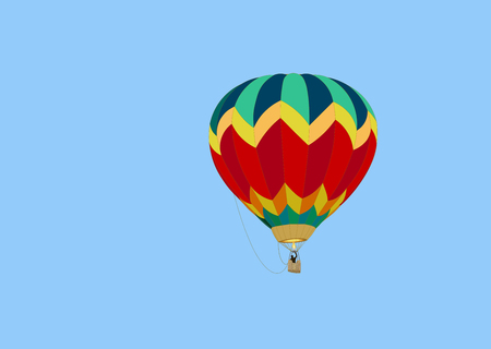 colorful balloon with a basket, a black silhouette of a man and a flame of fire from a burner, hovers in a blue sky on a summer day