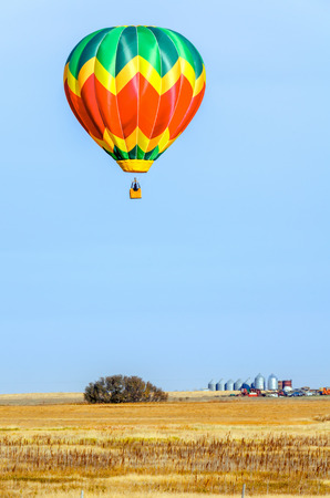 colorful balloon with a basket hovers over the yellow field on a summer day, tractor, truck, forest, farm and metal grain barns in the background