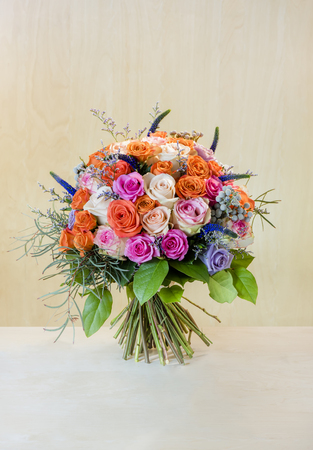 beautiful bouquet of flowers, multi-colored roses with green leaves stands on a light white table, brown background with a tree structure in the background
