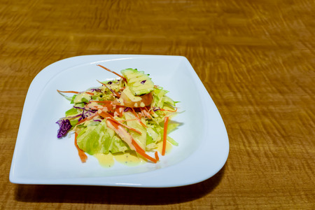 Appetizing salad of fresh vegetables on a white porcelain plate on a brown wooden table