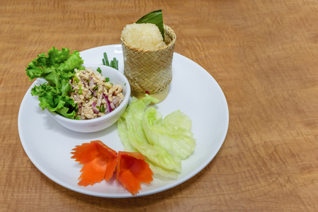 Top view of a delicious dish with Thai food. SALATHAI RICE SPECIAL. Stir-fried rice in the box, basil leaves, carrot, onion, cucumber on the white plate on the wood table