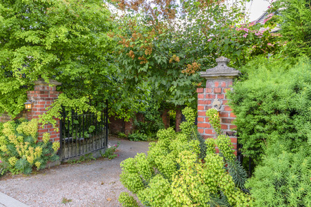 Open iron gates to the garden, brick walls, burning lights in front of the entrance, green bushes and trees, on a summer day