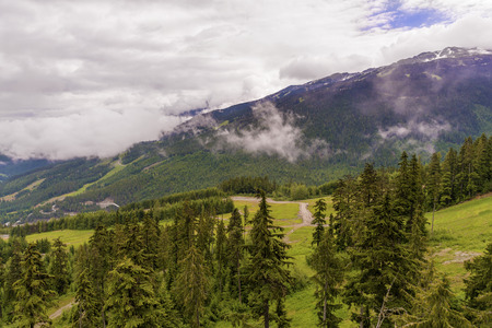 Fluffy white clouds over wooded mountains with country roads, coniferous trees and snow on top