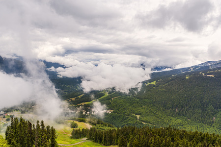 Top view of thick, fluffy white clouds over wooded mountains with country roads, coniferous trees and buildings on a summer day Reklamní fotografie