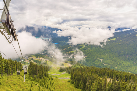 View from above on thick, fluffy white clouds over wooded mountains with country roads, coniferous trees, aerial ropeway and buildings on the grass on a summer day