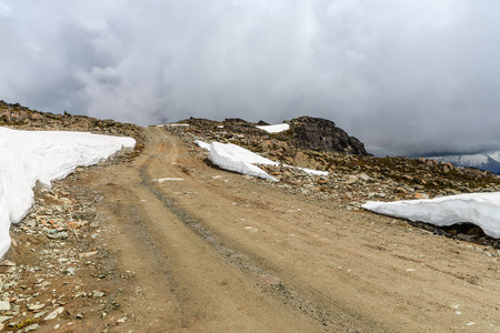 Dirt road, rocky road to the top of a rocky mountain covered with snowdrifts, a misty blue sky in the background with white clouds on a summer day
