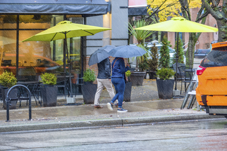 People man and a woman go with open umbrellas in the rain on the sidewalk down the street in the city past the glowing showcase cafe