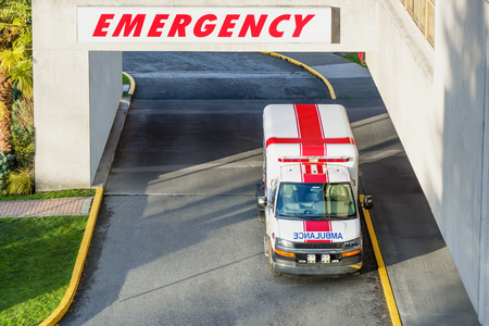 a view from the top of the entrance to the hospital and a modern ambulance with a red cross parked near the emergency entrance to the hospital in the afternoon, and is ready at any time to come to the rescue on call Editöryel
