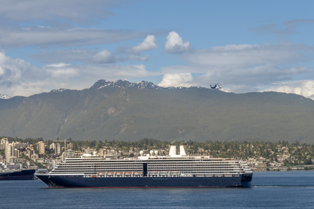 large ocean cruise liner sets sail from the modern seaside city. Mountains and blue sky with clouds, city buildings, flying helicopter in the background