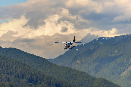 airplane, hydroplane flies in mountains covered with forest, under pink evening clouds and blue sky on a summer day