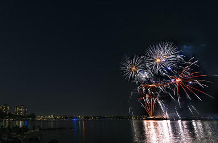 Multicolored fireworks over the ocean in the big city, silhouettes of people on the beach, modern buildings on the background, glowing and reflecting lights of the salute on the water Reklamní fotografie