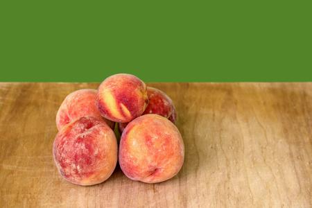 juicy, ripe fruit, peaches on a wooden board, green background Reklamní fotografie
