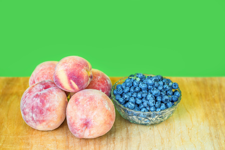 juicy, ripe shaggy peaches on a wooden board and fresh blueberries in a glass vase, green background