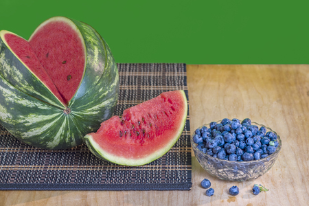 watermelon with red flesh and brown seeds and blueberries in a glass vase, on a wooden board with a wicker napkin, the green background is blurred