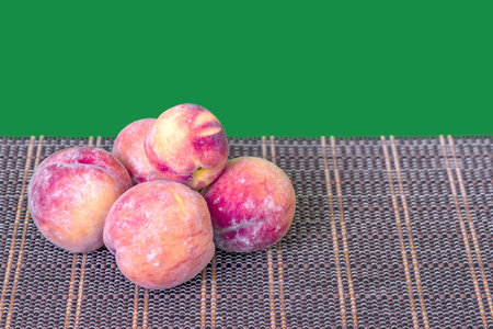 ripe, juicy fruits of peaches on a wicker brown rug, green background Reklamní fotografie