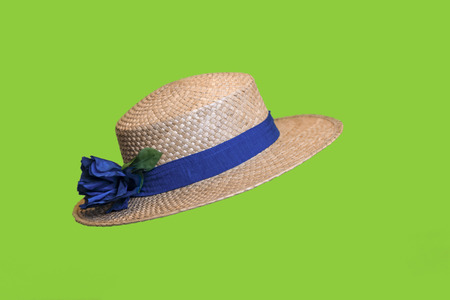 Stylish womens straw hat from sun with a blue ribbon  and with a beautiful bow, isolated on a green background.