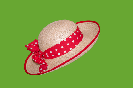 Stylish woman, straw hat with sun with red ribbon with white mugs and with a beautiful bow, isolated on a green background.
