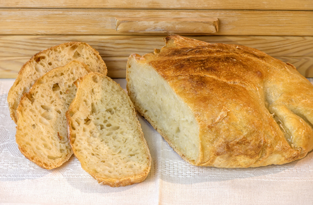 a loaf of freshly sliced white handicraft bread, on a table near a wooden breadbasket
