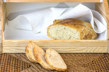 a loaf of freshly sliced white handicraft bread, in the wooden breadbox Reklamní fotografie