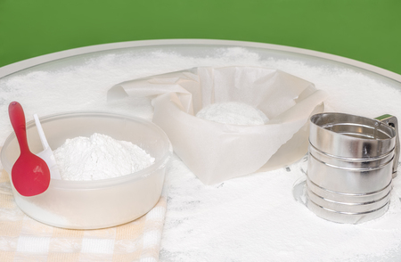 A table covered with flour, dough on a sheet of parchment paper, a plastic container with flour, a metal sieve, a red spoon, a linen towel on the table. Green blurred background.