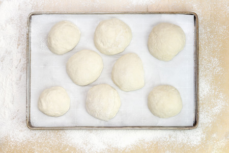 Balls of dough on parchment paper, on a metal tray on a wooden table covered with white flour. View from above.