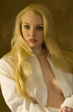 chica: blond with mans shirt open sitting looking at camera