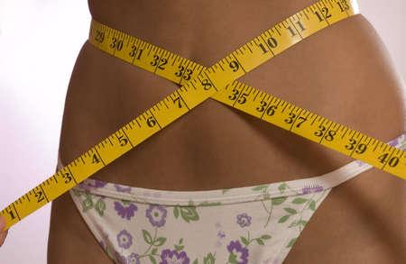 Hispanic girl measuring her self with tape photo