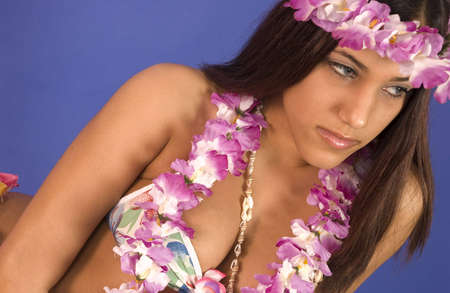Hispanic girl in a flower lay and grass skirt blue background 版權商用圖片 - 3006980