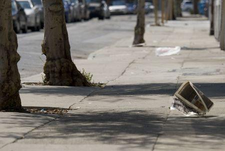 street corner: newspaper blowing down dirty street Stock Photo