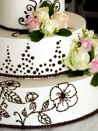 closeup details of beautiful tiered wedding cake with flowers photo