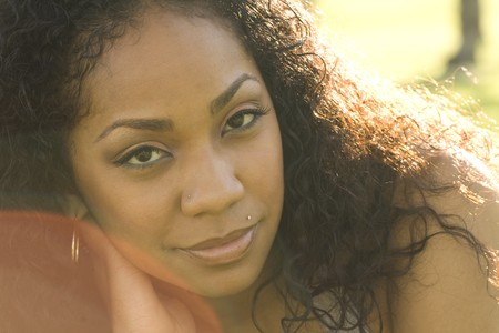 Beautiful portrait of a young black woman laying in grass on a sunny day with sun flare photo