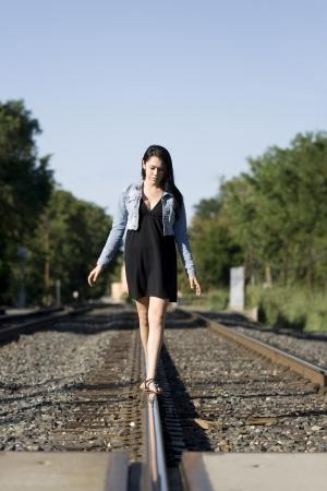Pretty teen walking alone on train tracks on a beautiful day photo
