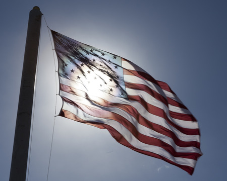 American Flag with sun glowing behind
