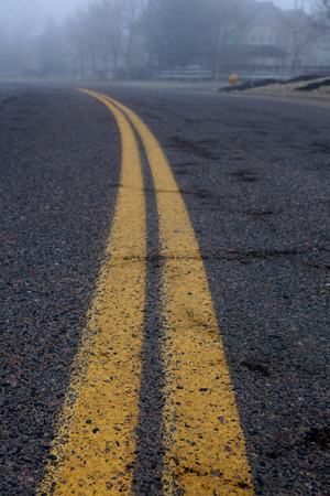 Two solid yellow lines on roadway Stock Photo