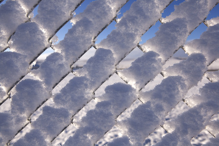 Close up of snowy fence showing diamond pattern Stock Photo