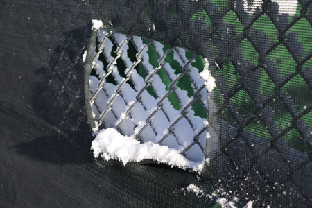 Snowy fence with cut out to baseball field Stock Photo