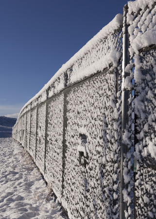 Snowy fence with blue sky Stock Photo