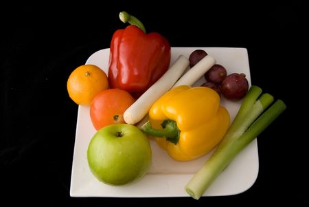 A plate of fresh fruits and vegetables on black background. photo