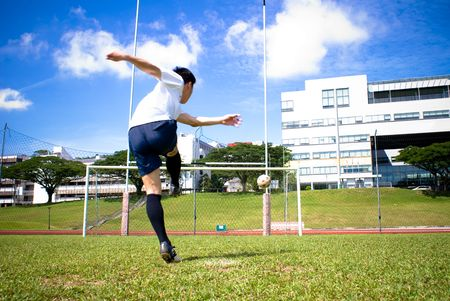 This photo captures the gesture when an asian male football player is shooting. Stock Photo