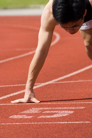 sich b�cken: Eine asiatische m�nnliche Athlet ist bereit zu starten. Seine abstrakten Sinne ist das Unternehmen bereit ist, alle Anforderungen, um loszulegen!  Lizenzfreie Bilder