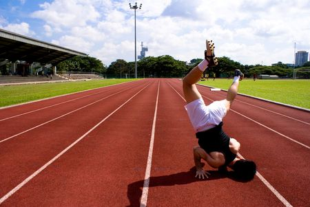 headstand: An asian male athlete in the red raceway with a headstand gesture to show his power and skills, muscle.