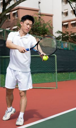 An Asian male tennis player is teeing off at the tennis court, wearing white tennis clothes.