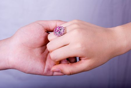 spousal: Hand in hand with a big purple diamond ring.