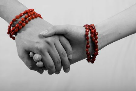 hand in hand with red bracelet in white background