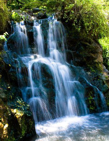 Relaxing landscaping waterfall in a green tropicl botanic garden
