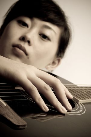 Asian girl devoted in playing wooden classic guitar