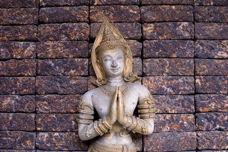 Golden praying budda on brick wall in thailand photo